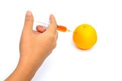 Syringing to orange. Isolated Orange liquid syring to orange fruit Stock Images