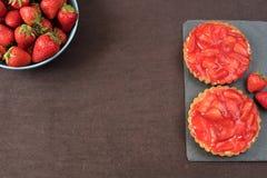 Syrlig choklad, tartaletten med vit choklad och mascarponen lagar mat med grädde, nya jordgubbar överst Stora blått bowlar mycket royaltyfri fotografi