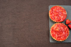 Syrlig choklad, tartaletten med vit choklad och mascarponen lagar mat med grädde, nya jordgubbar överst Svart bakgrund Töm utrymm royaltyfri bild