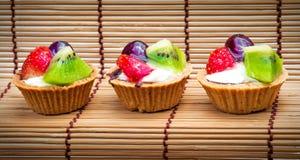Syrlig och träbakgrund för mini- frukt Arkivbild
