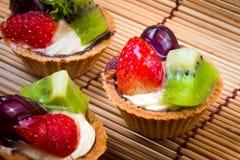 Syrlig och träbakgrund för mini- frukt Royaltyfria Bilder