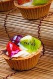 Syrlig och träbakgrund för mini- frukt Arkivfoto