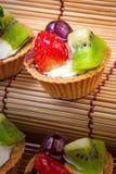 Syrlig och träbakgrund för mini- frukt Arkivfoton