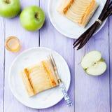 Syrliga Apple, smördegremsor med vaniljvaniljsås på en träbakgrund Royaltyfri Foto