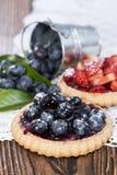 Syrliga blåbär och jordgubbe Royaltyfria Bilder