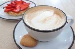 Syrliga cappuccino och jordgubbe arkivbilder