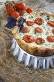 Syrligt med körsbärsröda tomater och ost på den aluminum bakningmaträtten Arkivfoto