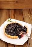 Syrligt snitt för hemlagat blåbär i fyrkantig vit platta med gaffeln och Royaltyfri Bild