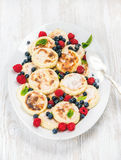 Syrniki or cottage cheese pancakes with fresh forest berries and sour cream sauce in serving dish over white wooden Stock Image