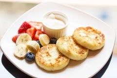 Syrniki de gâteaux au fromage du plat blanc avec les morceaux, la fraise et la myrtille de banane d'un plat avec la crème sure Fe Photographie stock