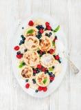 Syrniki o crepes del requesón con las bayas del bosque y la salsa de crema agria frescas en plato de porción sobre de madera blan Foto de archivo libre de regalías