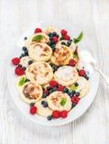 Syrniki o pancake della ricotta con le bacche della foresta e la salsa di panna acida fresche nel piatto di servizio sopra di leg Immagine Stock