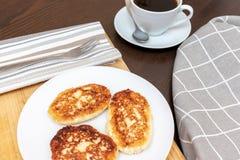 Syrniki o sirniki ruso, buñuelos hechos en casa del requesón o crepes desayuno con los pankakes de la cuajada y una taza de café fotos de archivo libres de regalías