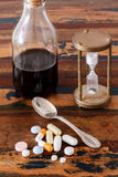 Syrup in glass bottle, pills and vintage hourglass Royalty Free Stock Photography
