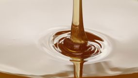 Syrup Pours Artistic Closeup. Honey pours onto plain white surface - cookery concept stock video footage