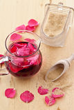 Syrup with rose petals. Pink syrup with fresh rose petals on wooden table royalty free stock photos