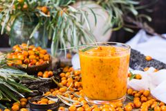 Syrup of seabuckthorn berries in a glass. On a wooden table Stock Photos