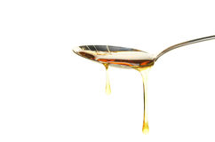Syrup in spoon. Syrup drips from a spoon isolated against white stock photo
