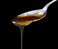 Syrup on spoon. Syrup dripping off a spoon on black background Stock Photo