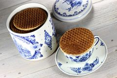 Syrup waffles. Traditional dutch syrup waffles with delftware on wooden background Stock Photo