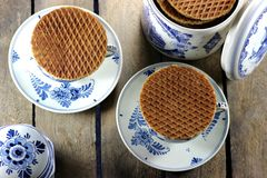 Syrup waffles. Traditional dutch syrup waffles with delftware on wooden background Royalty Free Stock Image