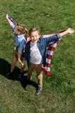 Syskon med amerikanska flaggan som har rolig det fria som firar 4th juli - självständighetsdagen Royaltyfri Bild