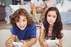 Syskon med fjärrkontrollen som spelar videospel på matta Royaltyfri Bild