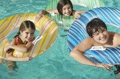 Syskon med uppblåsbara flottar som tillsammans tycker om i simbassäng royaltyfri fotografi
