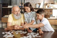 Syskon och deras farfar som monterar ett pussel Arkivfoto