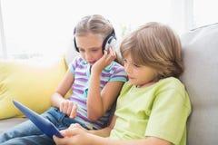 Syskon som använder den digitala minnestavlan medan lyssnande musik Arkivfoton