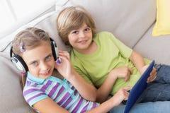Syskon som använder den digitala minnestavlan medan lyssnande musik på soffan Fotografering för Bildbyråer
