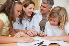 Syskon som får hjälp med läxa från föräldrar Fotografering för Bildbyråer