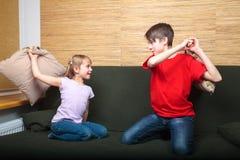 Syskon som har kuddekamp på en soffa arkivbild