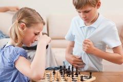 Syskon som leker schack Arkivbild
