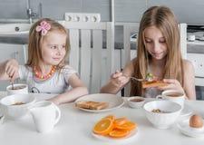 Syskon som sätter honung på rostade bröd, sunda foods Arkivbilder