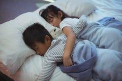 Syskon som sover på säng i sängrummet Royaltyfria Bilder