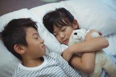 Syskon som sover på säng i sängrummet Royaltyfria Foton
