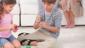 Syskon som spelar brädeleken på golvet Royaltyfria Foton