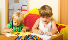 Syskon som spelar med blyertspennor Royaltyfri Bild