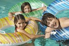 Syskon som tillsammans tycker om i simbassäng arkivbild