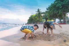 Syskonbarn spelar med v?gen och sand i den Pattaya stranden Thailand arkivfoto