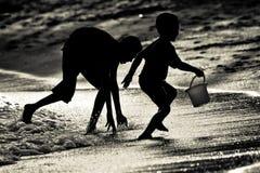 Syskonbröder som spelar att fånga på en strand i Singapore royaltyfri fotografi