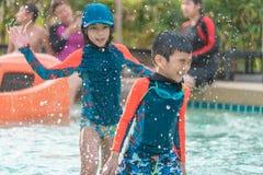 Syskonet ?r k?ra och jaga i simbass?ng royaltyfri foto