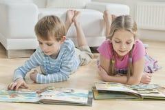Syskonet som läser berättelse, bokar på golv i vardagsrummet Royaltyfri Fotografi