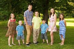 Syskonet som står i en familj, poserar Royaltyfri Foto