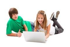 Syskonet surfar upp internet, pojketummar - isolerat på vit Arkivfoton