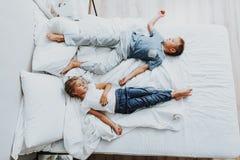 Syskongrupp som sover på säng, når att ha spelat royaltyfri foto