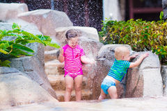 Syskongrupp som spelar med vattenklappet utomhus Arkivbild