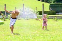 Syskongrupp som spelar med vattenslangen i trädgården Royaltyfria Foton
