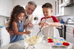 Syskongruppanseende på köksbordet som gör kakablandningen med deras farfar, slut upp arkivbilder